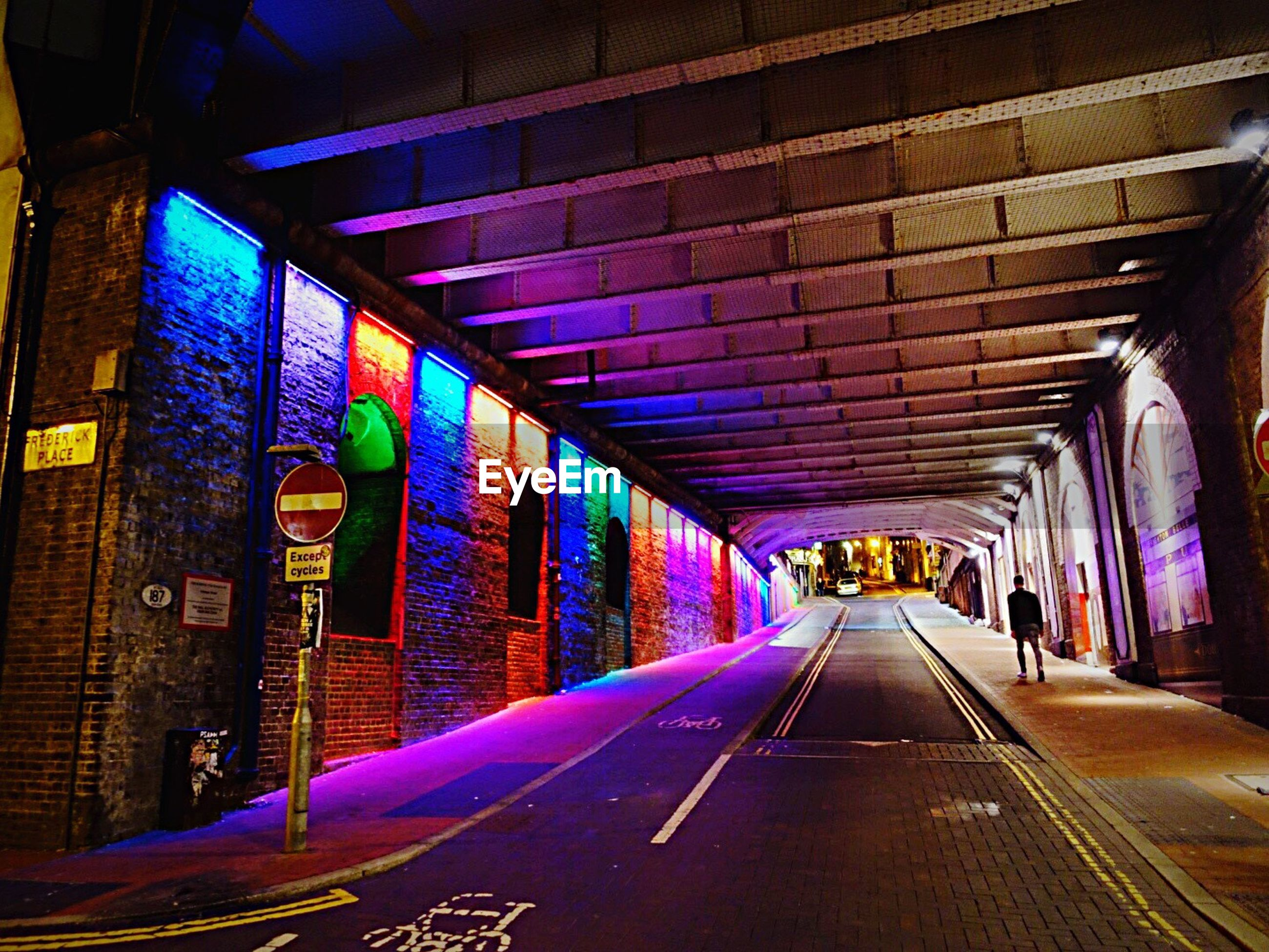 Rear view of man walking in illuminated multi colored tunnel