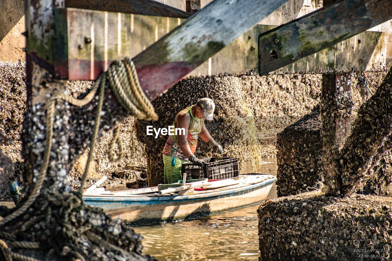 water, nature, nautical vessel, sunlight, day, transportation, one person, waterfront, real people, outdoors, adult, mode of transportation, side view, built structure, women, motion, architecture, wheel