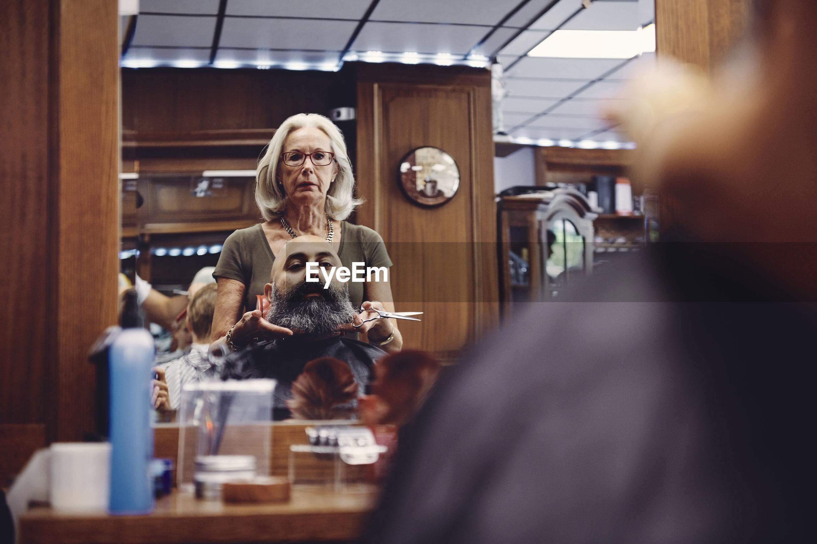 Woman cutting bald man beard in hair salon