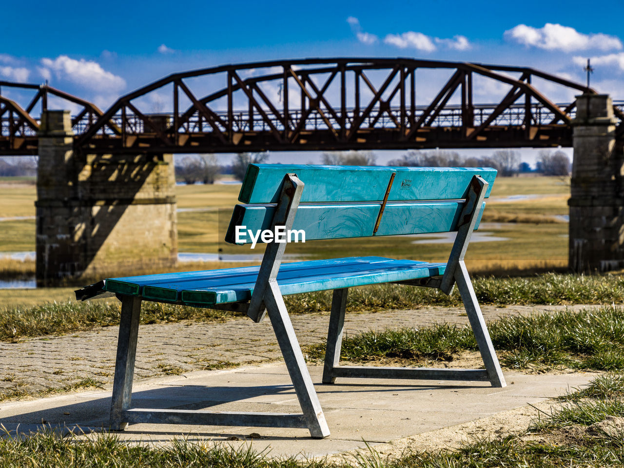 Blue Empty Bench Against Bridge