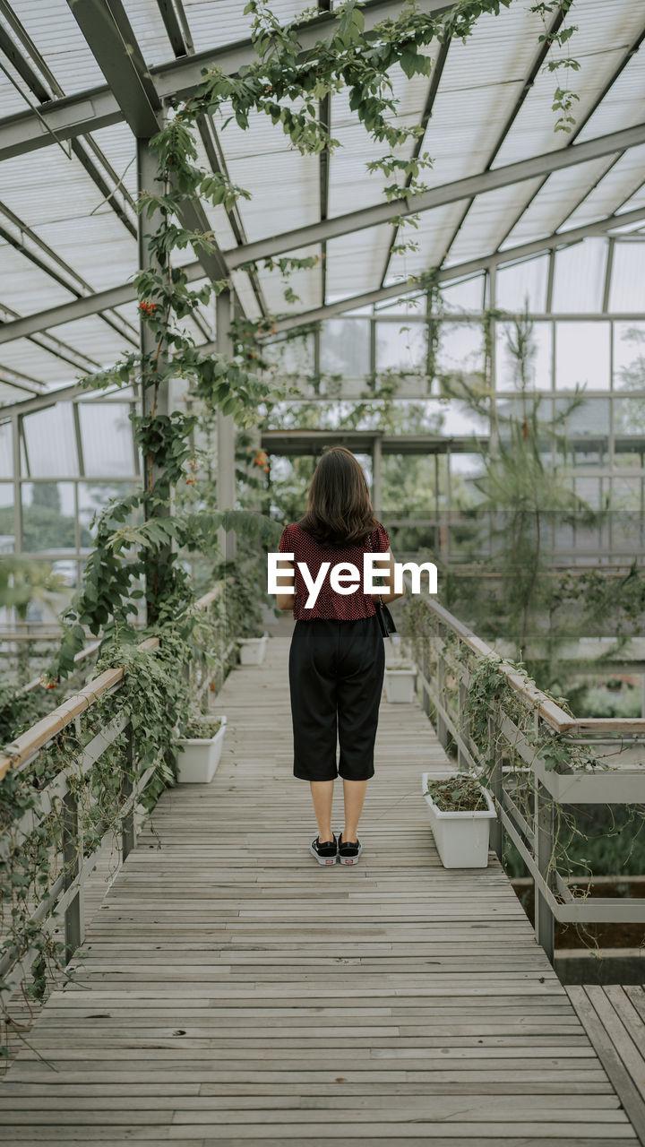 FULL LENGTH REAR VIEW OF WOMAN STANDING AT FOOTBRIDGE
