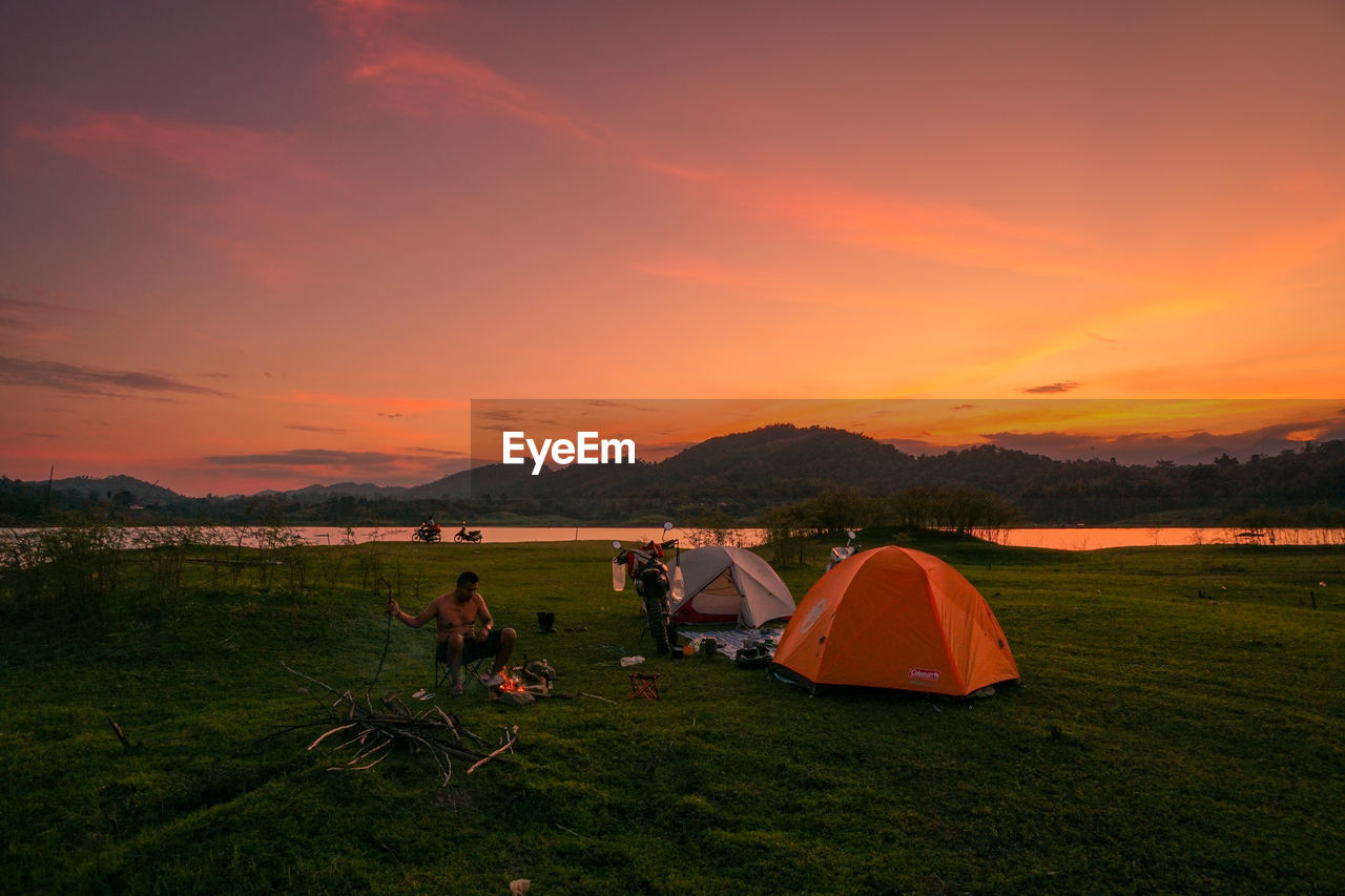 sunset, sky, orange color, tent, camping, beauty in nature, land, scenics - nature, nature, grass, field, leisure activity, environment, landscape, non-urban scene, people, adventure, real people, holiday, mountain
