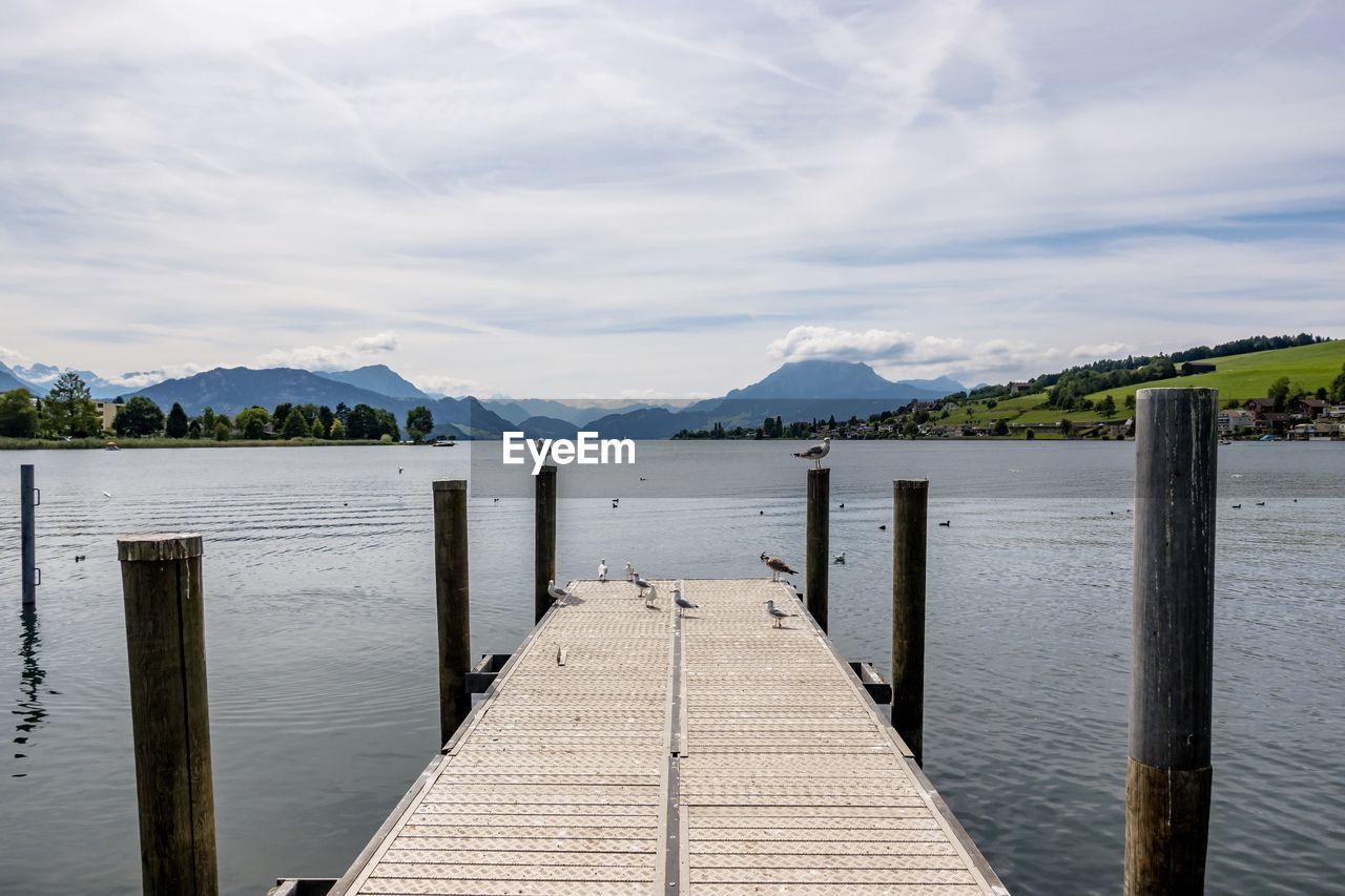 water, sky, cloud - sky, mountain, scenics - nature, wood - material, lake, beauty in nature, pier, tranquility, nature, direction, tranquil scene, the way forward, day, no people, built structure, post, idyllic, outdoors, wooden post, wood, wood paneling, long