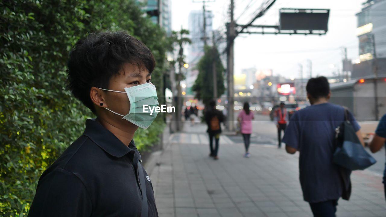 Man Wearing Pollution Mask Standing On Sidewalk In City