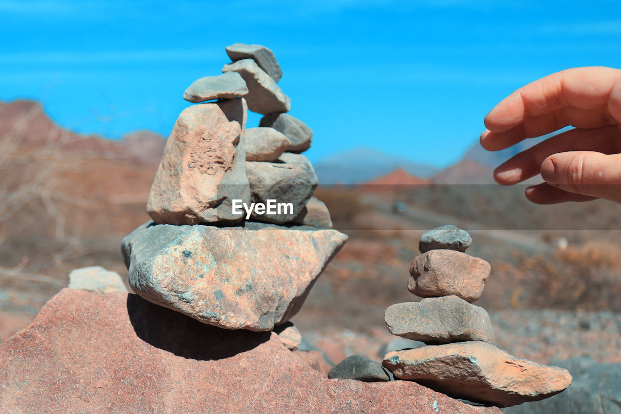 Close-up of hand stacking stones against mountains