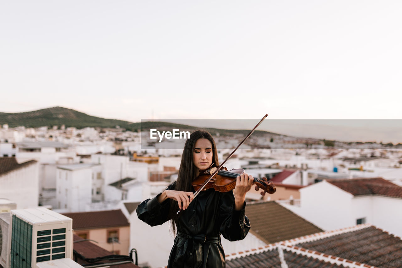 YOUNG WOMAN STANDING AGAINST CITYSCAPE