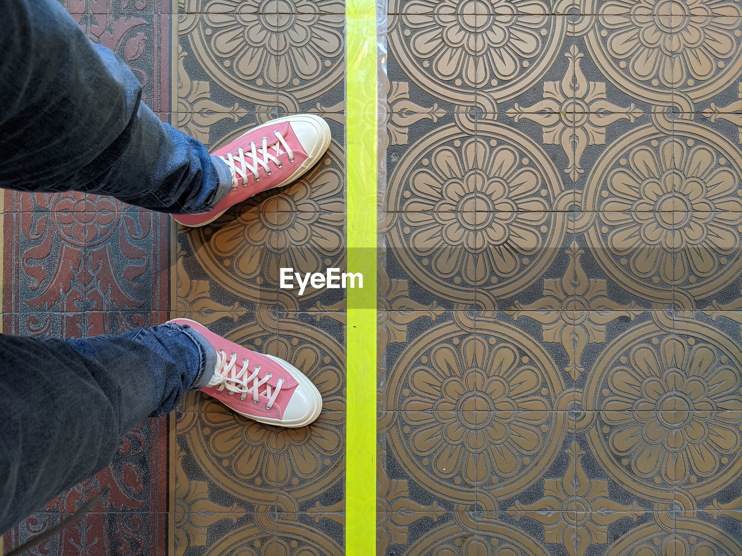 LOW SECTION OF PEOPLE STANDING ON TILED FLOOR