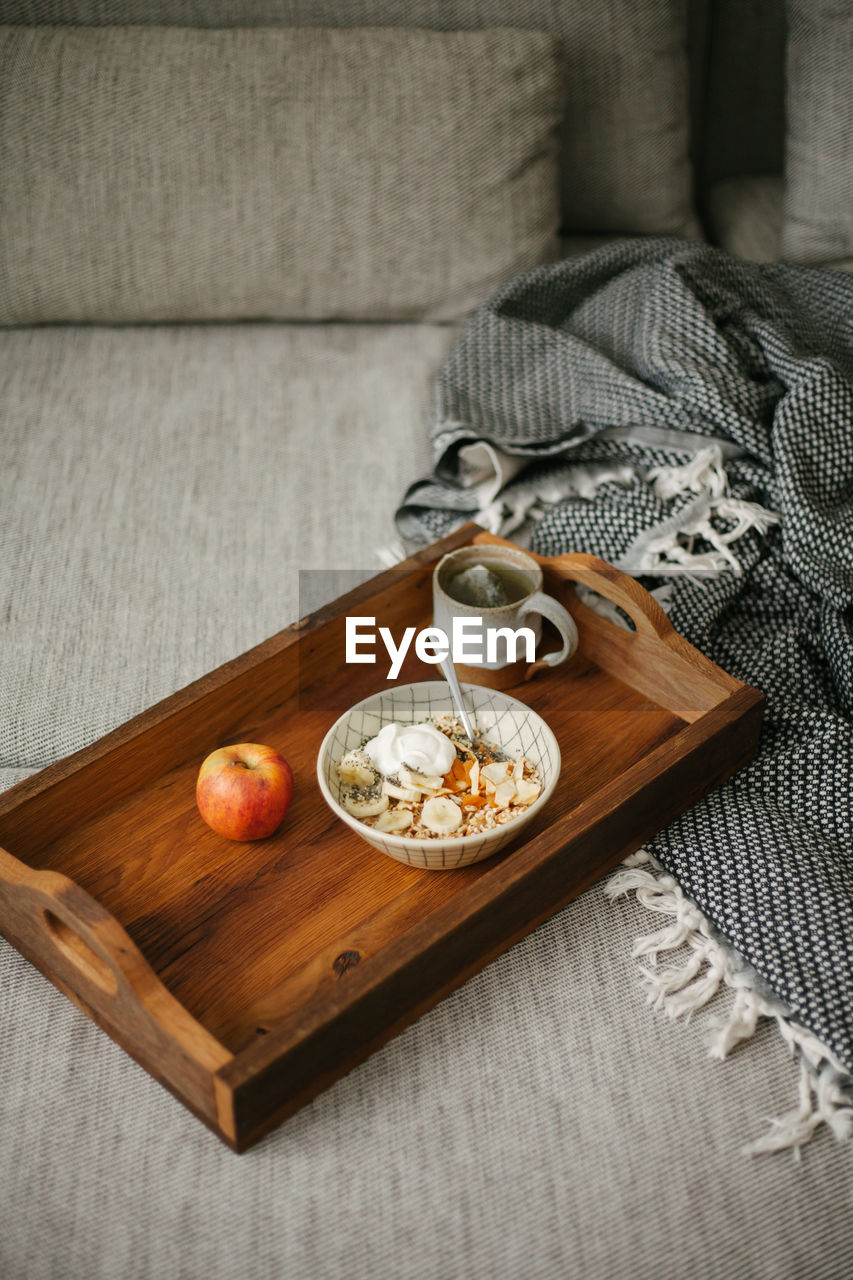 HIGH ANGLE VIEW OF BREAKFAST ON TABLE AGAINST WOODEN WALL