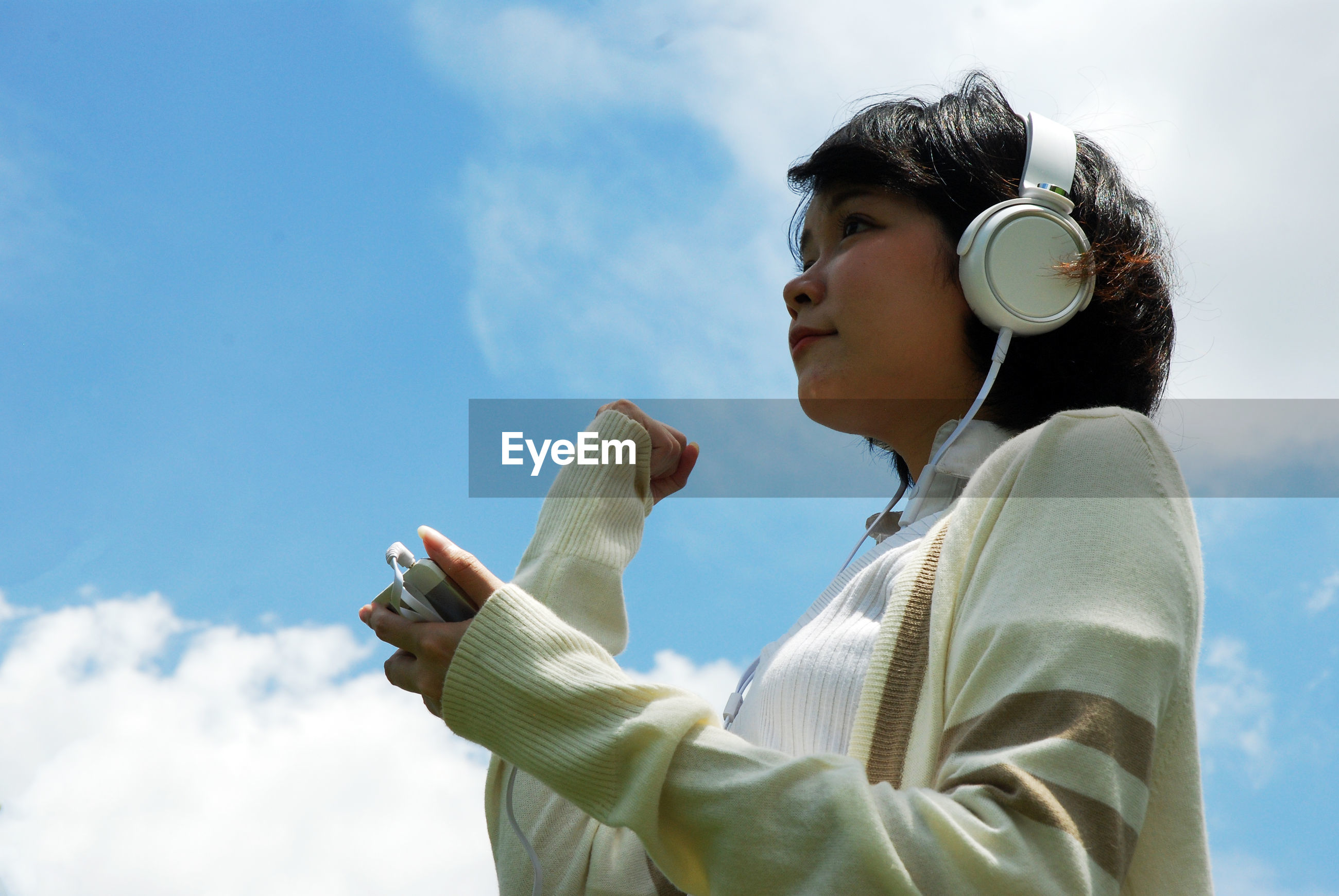 Low angle view of woman listening to music against sky