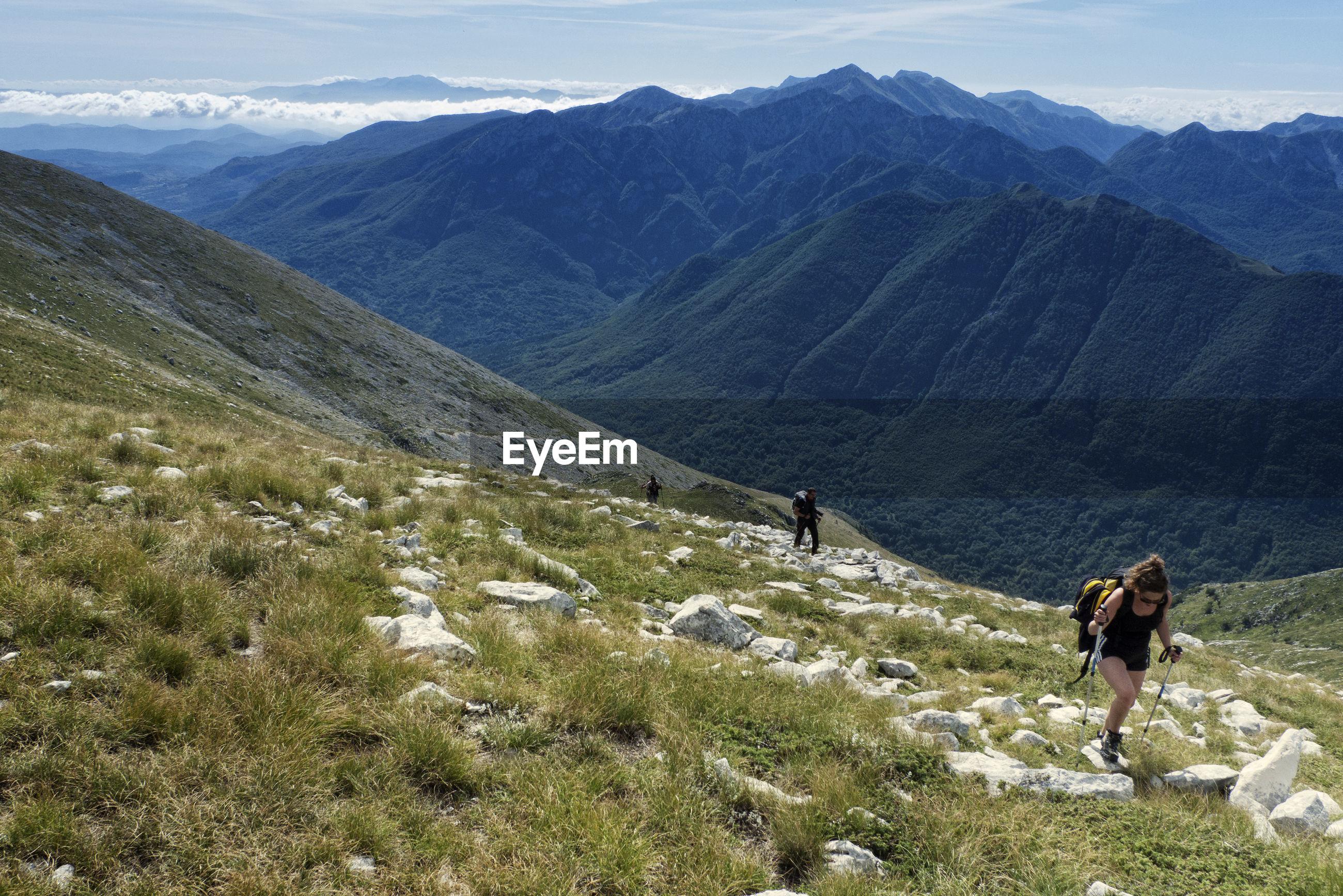 PEOPLE WALKING ON MOUNTAIN RANGE