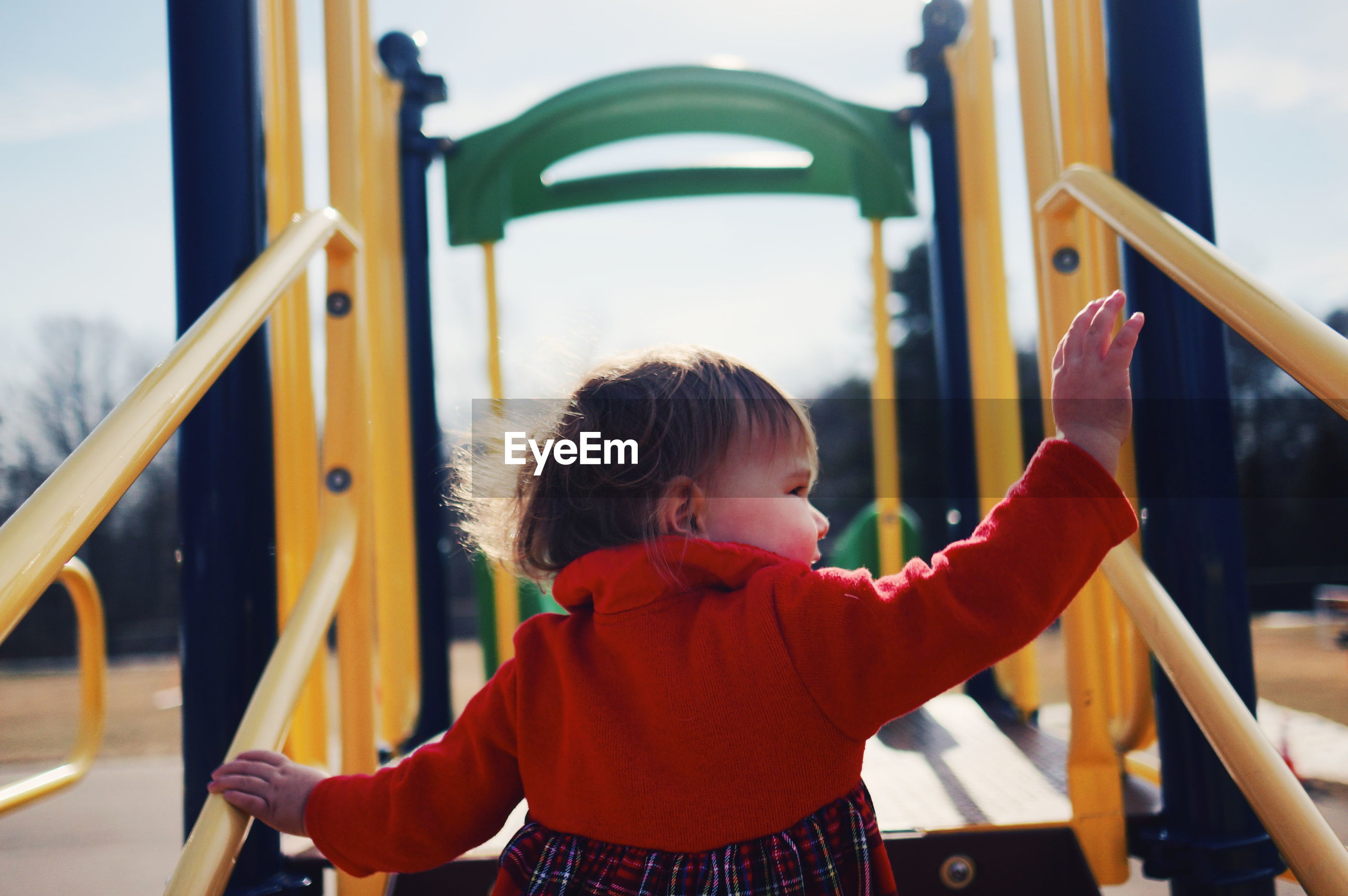 Rear view of toddler baby playing at playground