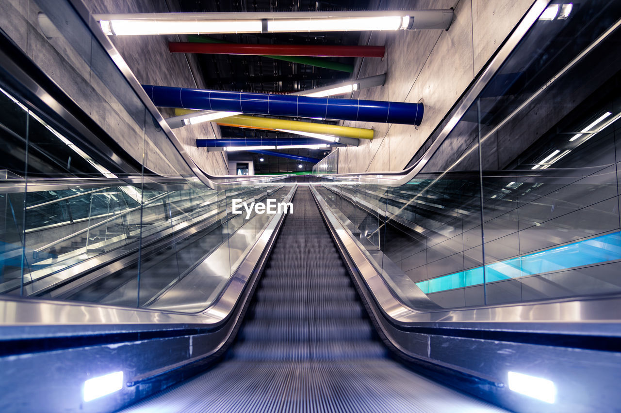 escalator, transportation, architecture, indoors, staircase, convenience, futuristic, railing, illuminated, modern, motion, technology, the way forward, steps and staircases, moving walkway, connection, direction, subway station, on the move, no people, diminishing perspective, ceiling