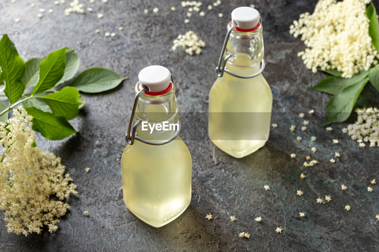 bottle, container, high angle view, no people, food and drink, table, glass - material, seasoning, olive oil, salt - seasoning, food, salt shaker, ingredient, nature, focus on foreground, still life, oil, plant part, freshness, leaf