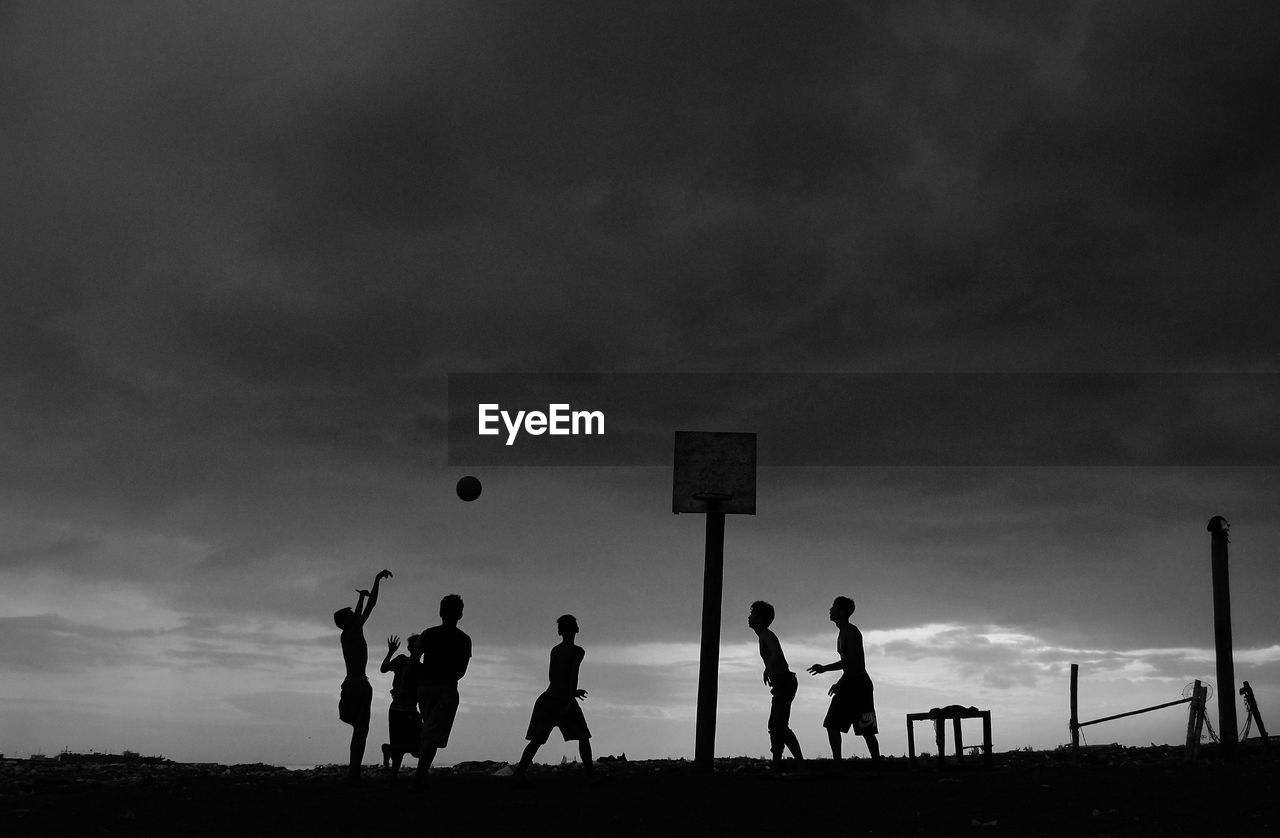 Silhouette boys playing basketball against sky