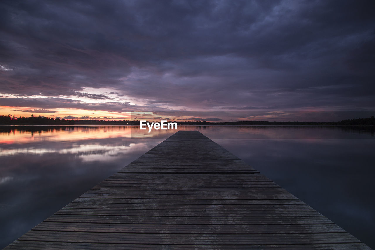 Jetty Over Lake Against Cloudy Sky During Sunset