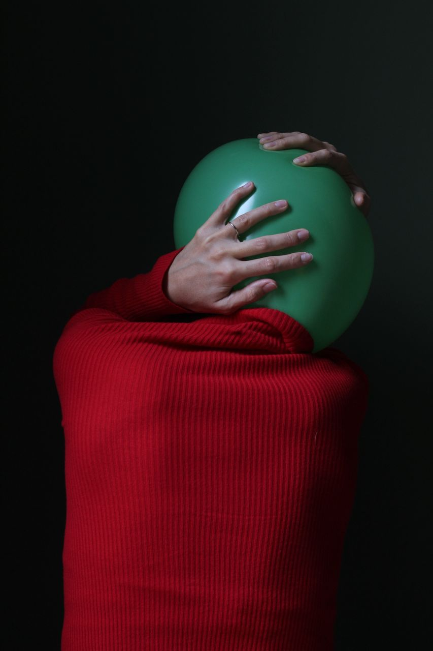 indoors, studio shot, red, one person, black background, standing, copy space, green color, human body part, close-up, clothing, rear view, headshot, unrecognizable person, young adult, adult, sweater, casual clothing, obscured face, human face