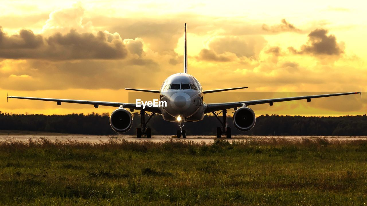 air vehicle, sky, cloud - sky, mode of transportation, transportation, nature, land, airplane, sunset, field, no people, grass, plant, travel, public transportation, airport, outdoors, environment, orange color, flying
