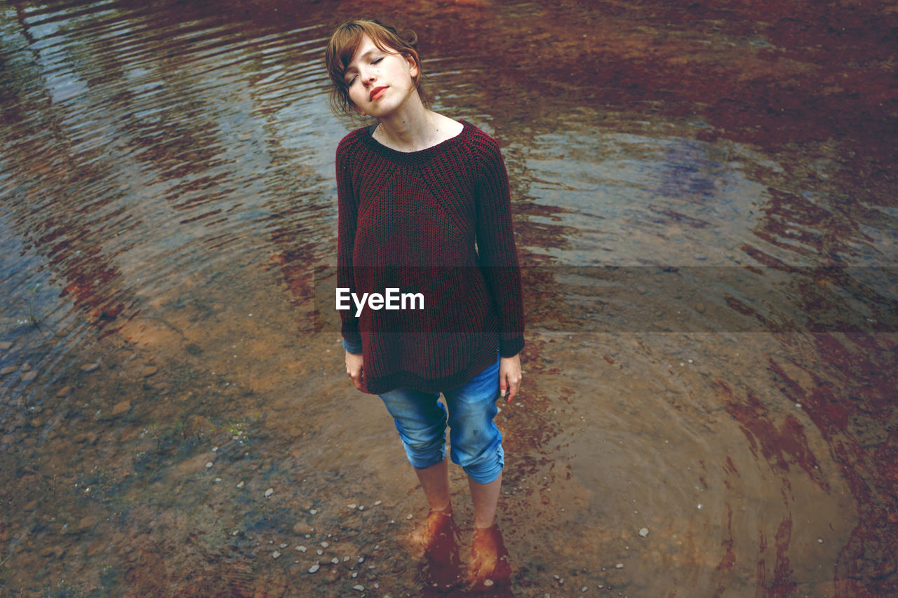 Full Length Of Woman With Eyes Closed Standing In Lake