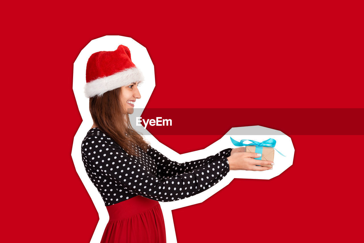 Smiling woman holding gift box against red background