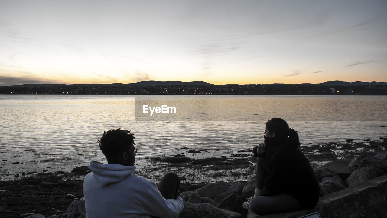 REAR VIEW OF PEOPLE SITTING ON SHORE AGAINST SKY DURING SUNSET