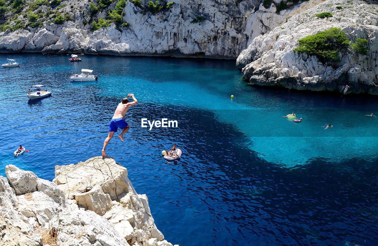 HIGH ANGLE VIEW OF SHIRTLESS MAN JUMPING IN SEA