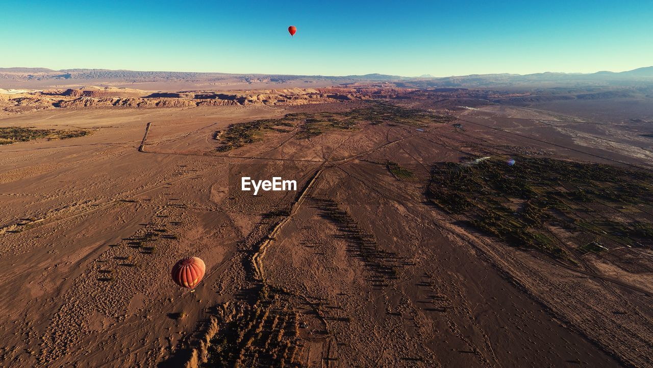 landscape, environment, balloon, hot air balloon, air vehicle, scenics - nature, transportation, beauty in nature, land, nature, sky, mountain, non-urban scene, tranquil scene, flying, mode of transportation, adventure, mid-air, travel, day, no people, outdoors, climate, arid climate