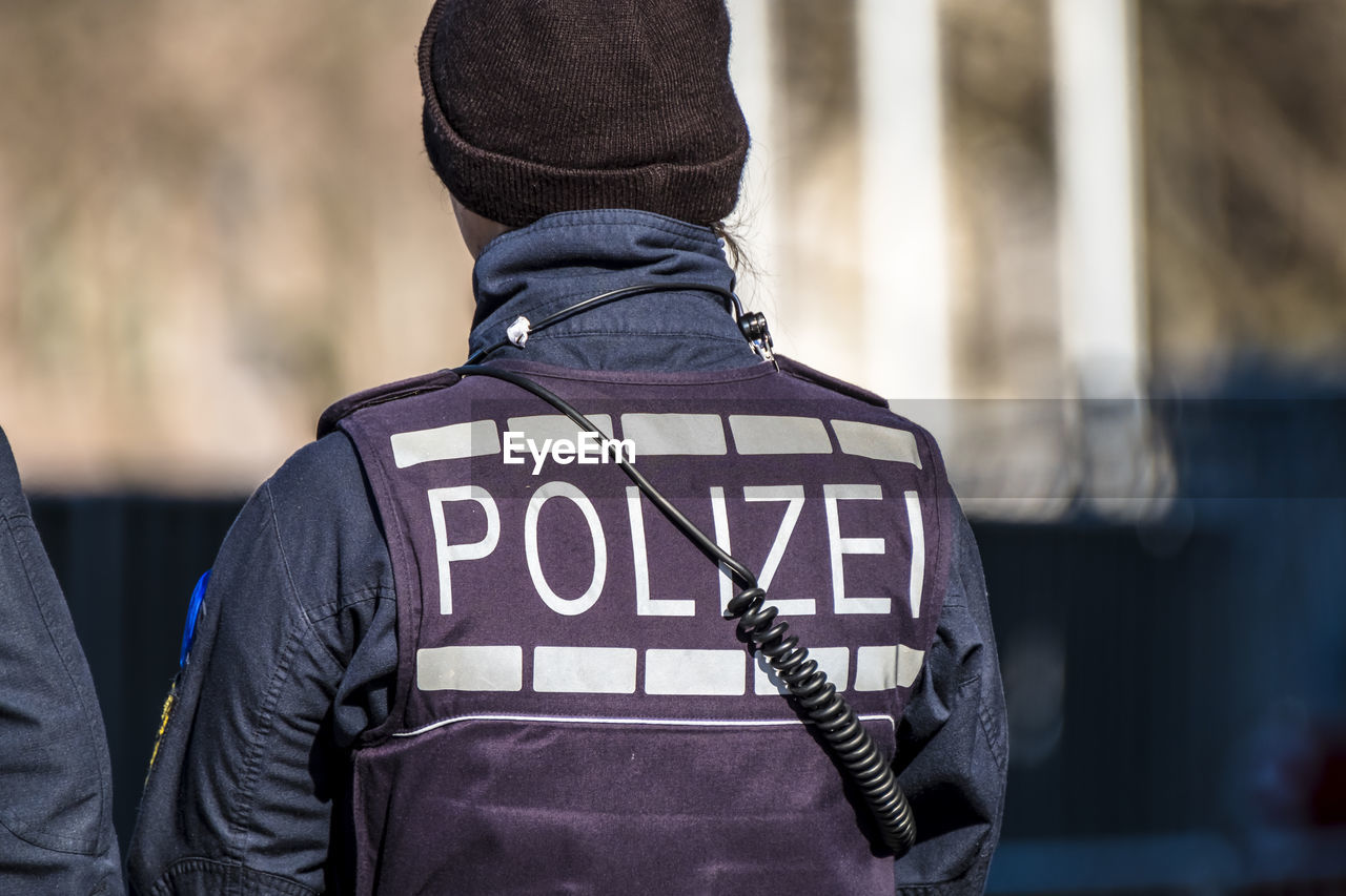 rear view, police force, real people, police uniform, text, jacket, uniform, men, focus on foreground, communication, outdoors, day, occupation, one person, people