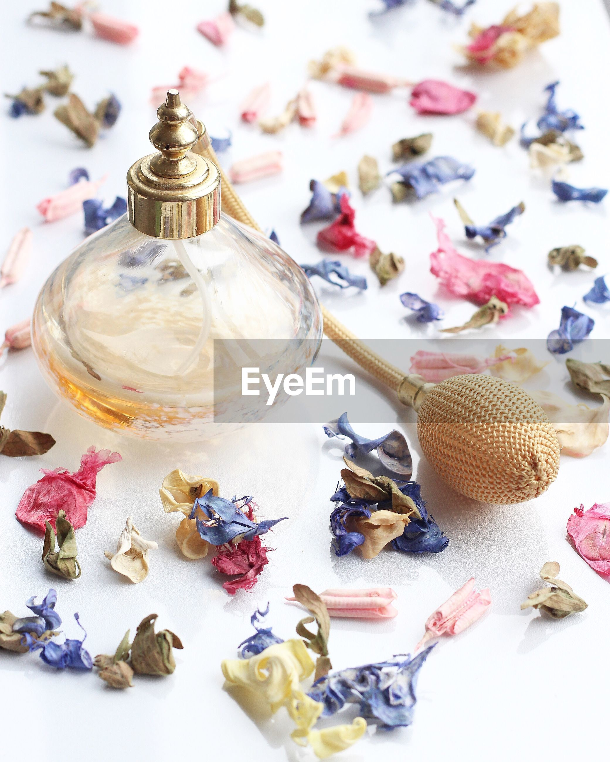 Close-up of perfume bottle and petals on table