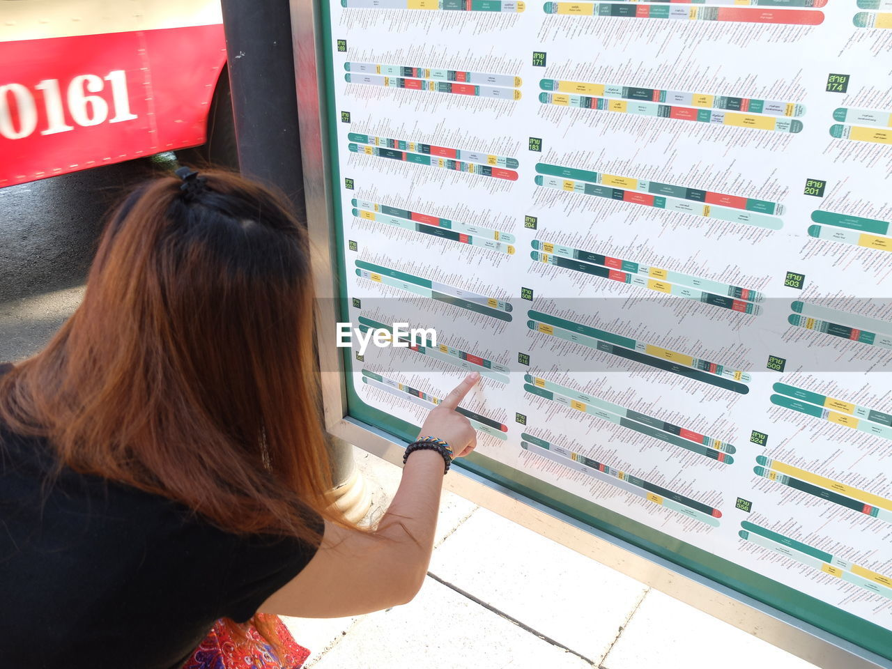 Rear view of woman pointing at colorful chart