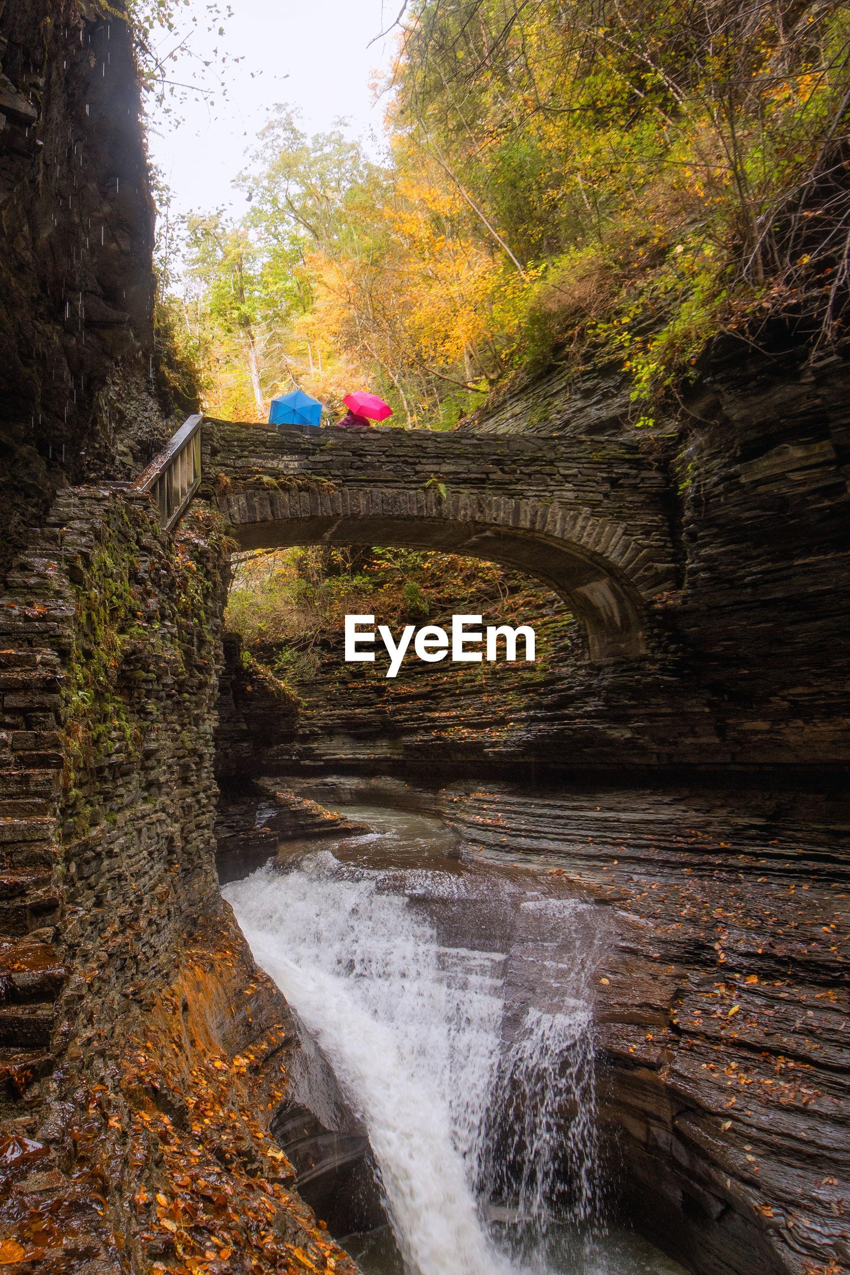 Waterfall below arch bridge in forest