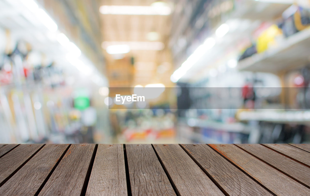 wood - material, indoors, focus on foreground, no people, table, in a row, empty, illuminated, day, arrangement, architecture, close-up, business, side by side, selective focus, flooring, seat, pattern, absence