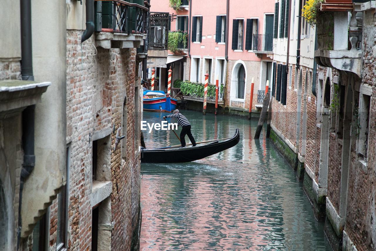 Gondolier Sailing Gondola In City Amidst Buildings