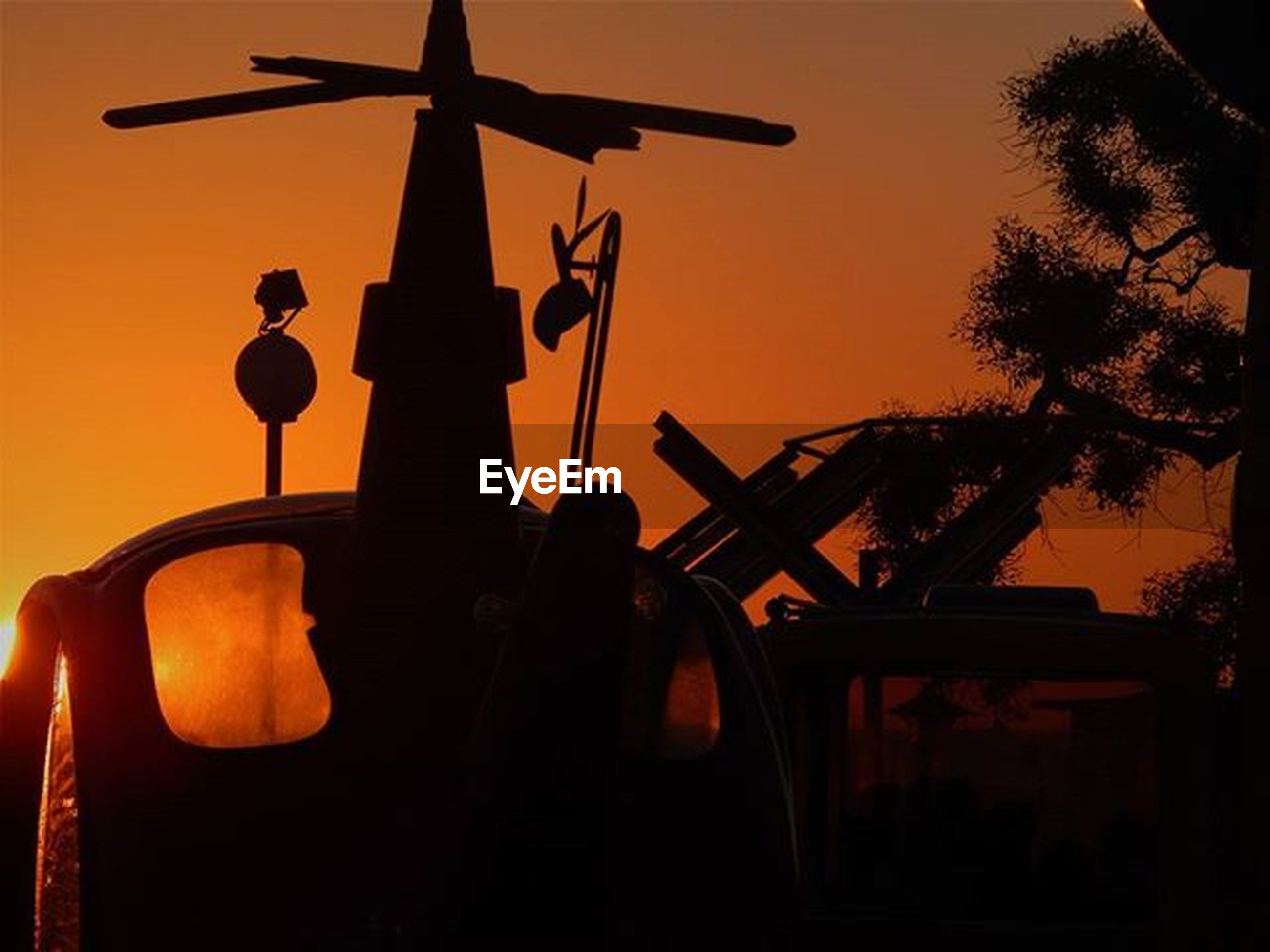 sunset, silhouette, orange color, low angle view, sky, transportation, mode of transport, dusk, clear sky, fuel and power generation, technology, sun, windmill, outdoors, environmental conservation, air vehicle, no people, airplane, nature, street light