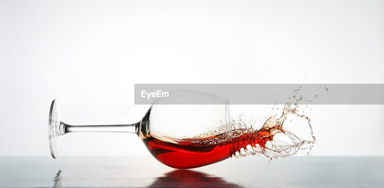 Close-up of red wine spilling from glass against white background