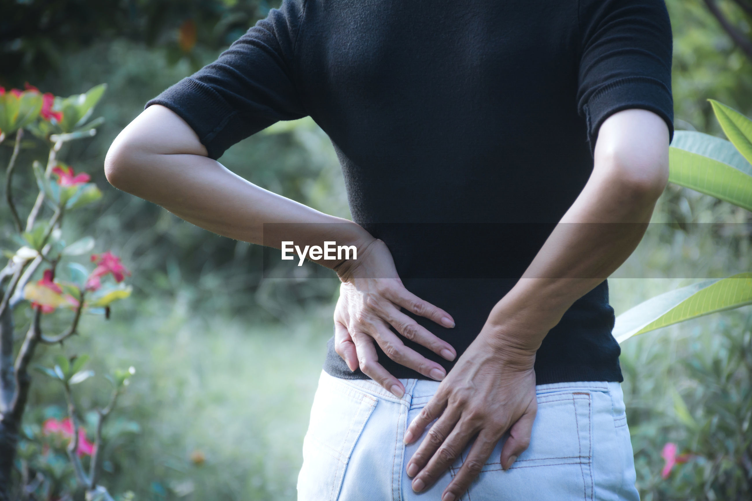 Rear view of woman touching back in pain while standing by plants