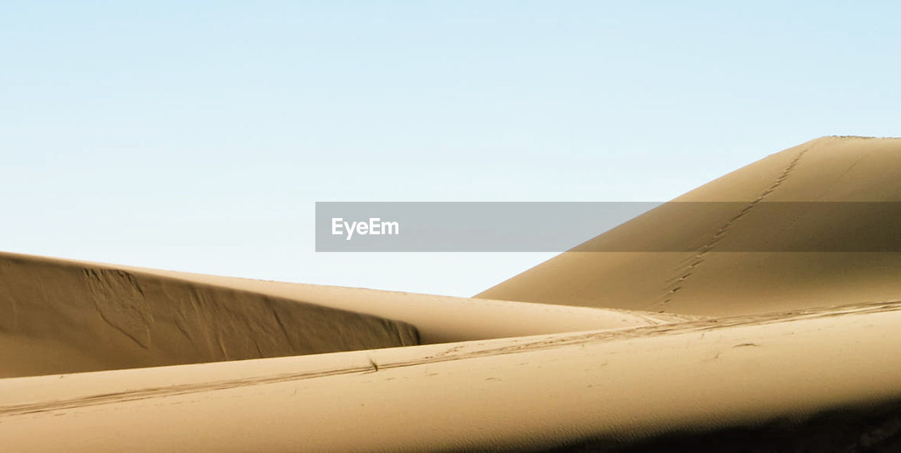 sky, clear sky, copy space, day, nature, transportation, desert, mode of transportation, no people, airplane, low angle view, sunlight, air vehicle, travel, blue, land, outdoors, sand dune, brown, sand, arid climate, climate