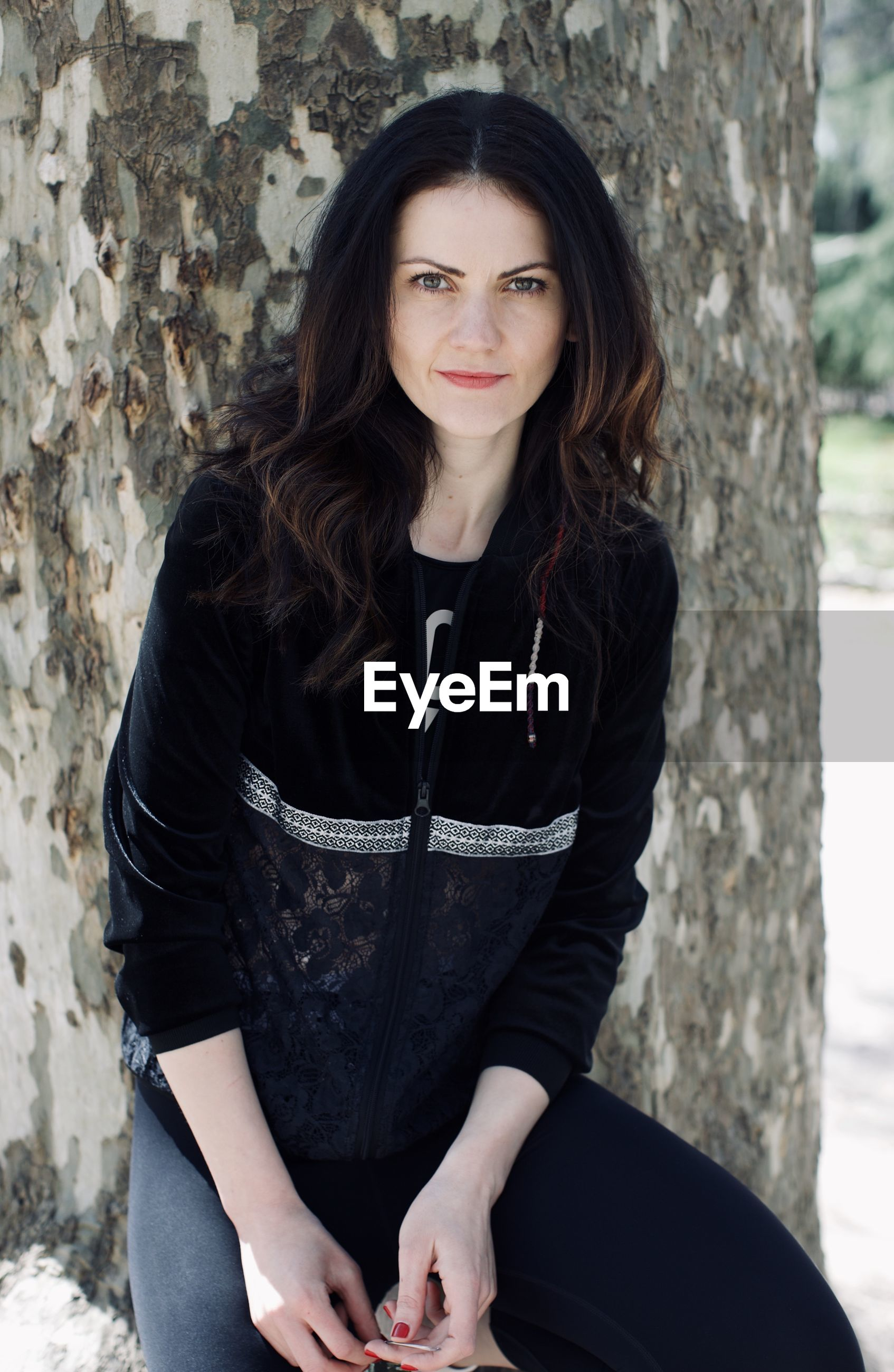 Fashionable mid adult woman wearing black clothing against tree trunk