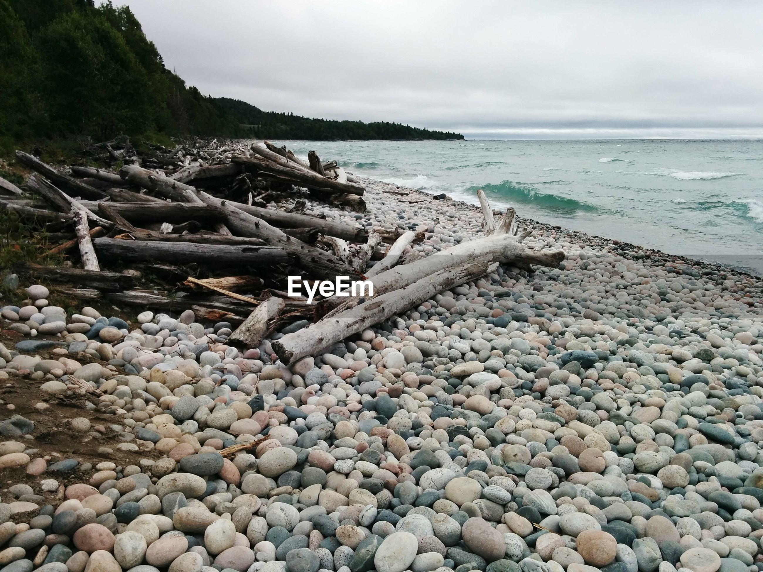 Pebbles on beach against cloudy sky