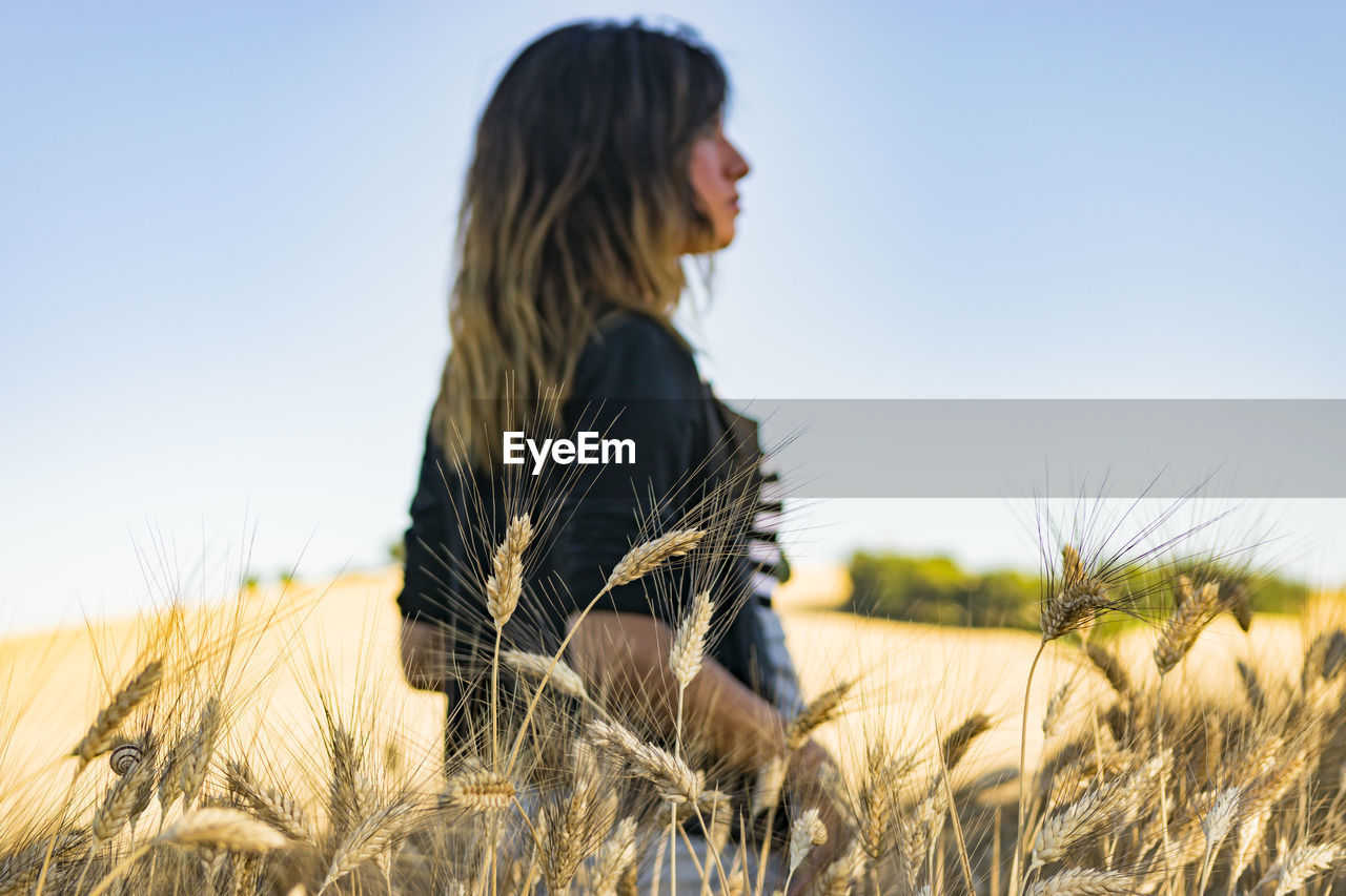 Side View Of Young Woman In Field Against Clear Sky