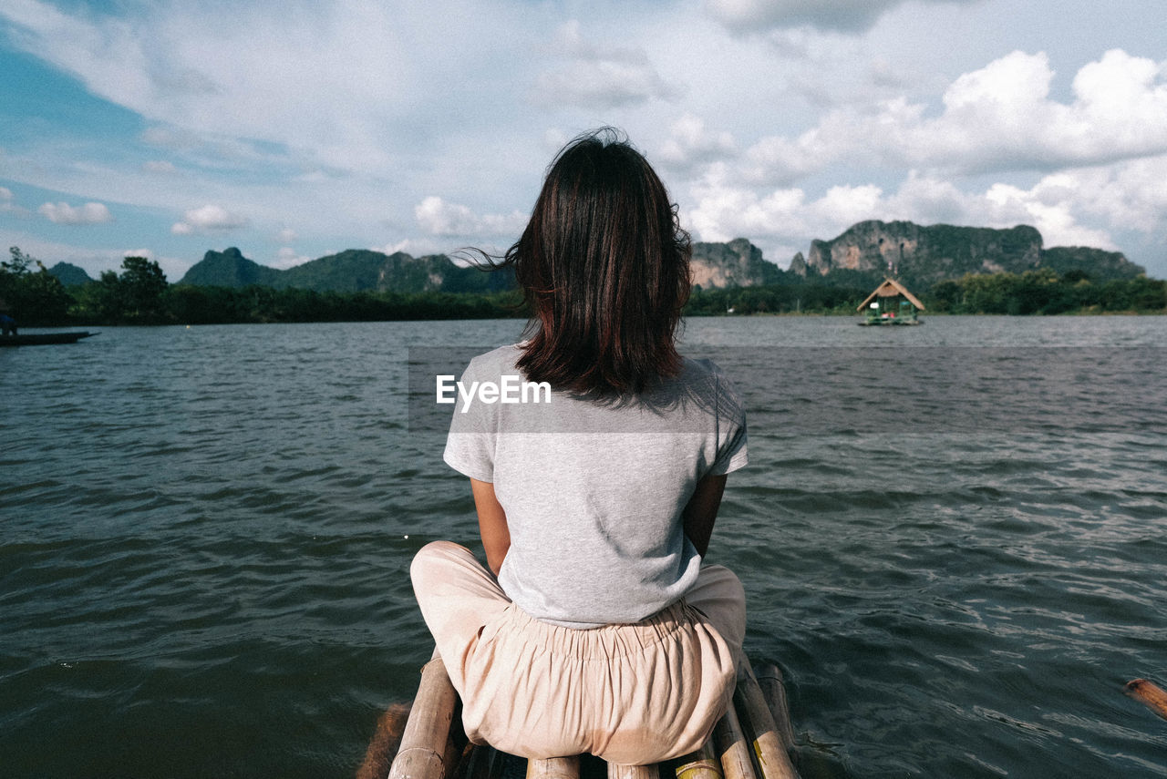 Woman sitting on wooden raft over lake against sky