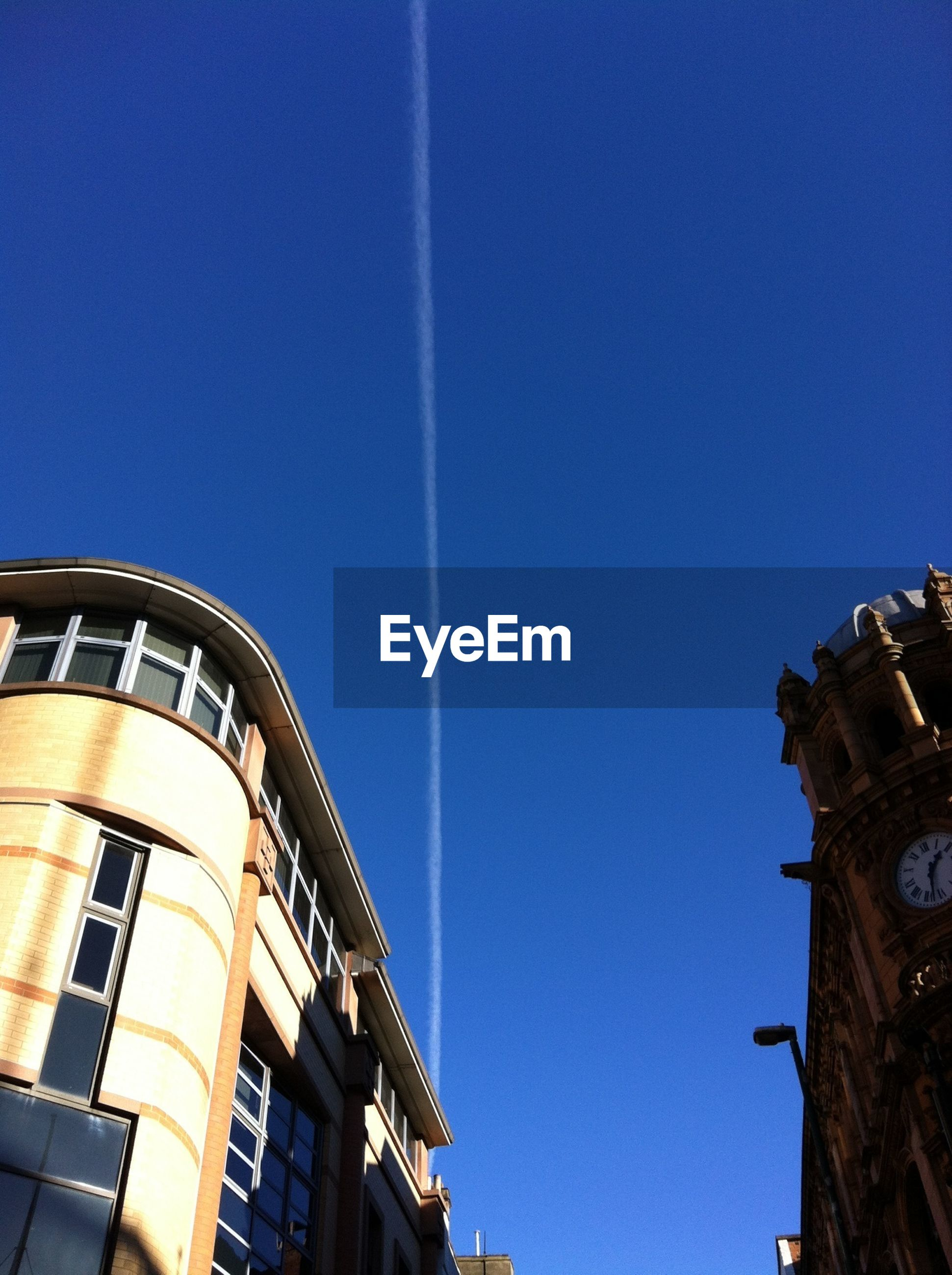 Low angle view of buildings against vapor trail in clear blue sky