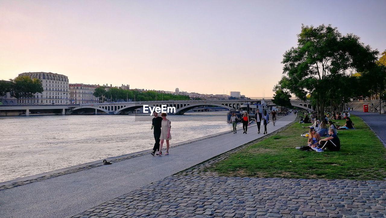 PEOPLE WALKING ON BRIDGE IN CITY AGAINST SKY