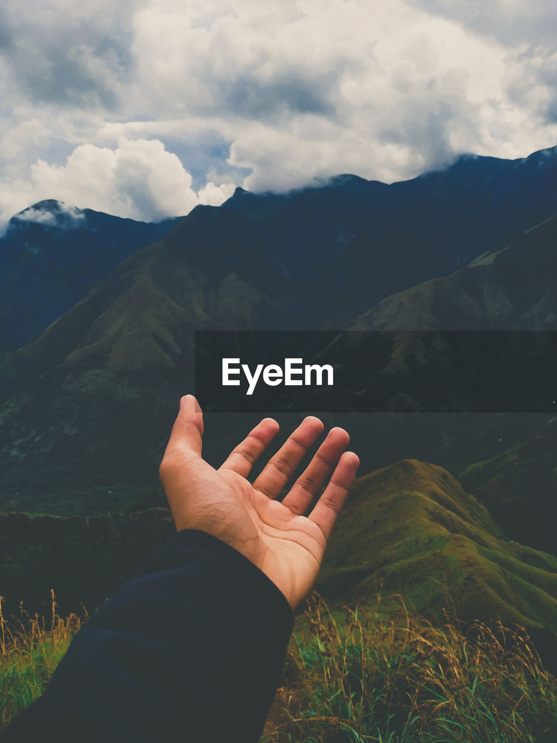Cropped hand of person gesturing against mountains and sky