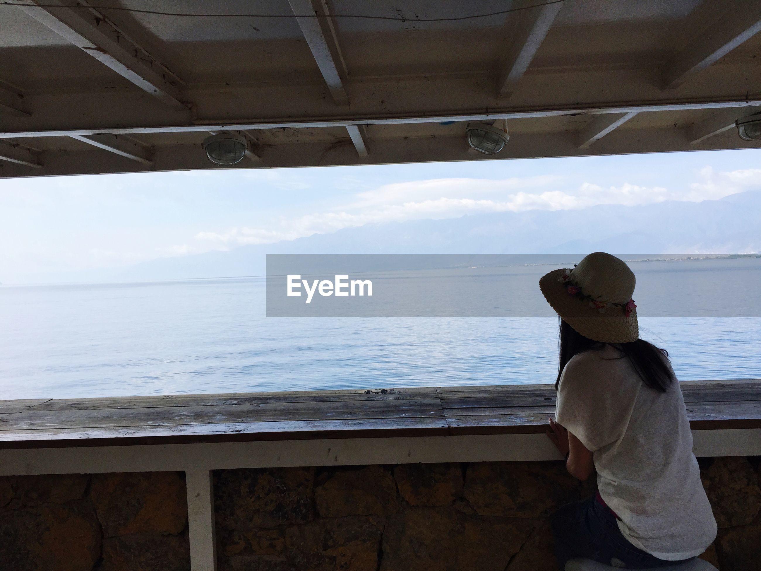 water, sea, lifestyles, standing, leisure activity, rear view, horizon over water, casual clothing, sky, sitting, full length, three quarter length, day, person, looking at view, sunlight, men, travel