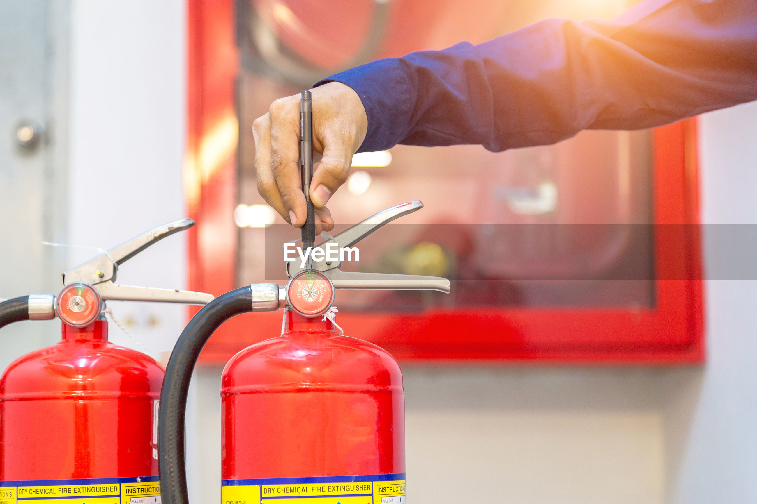 Midsection of person working with red wine fire extinguisher