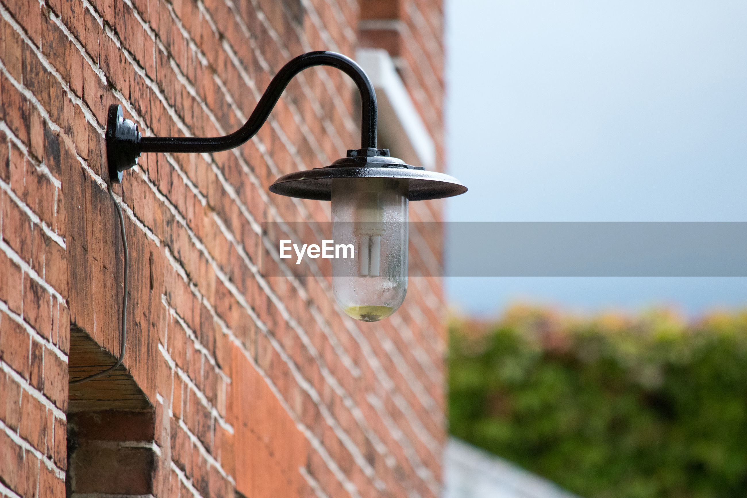 Low angle view of lighting equipment on brick wall against clear sky
