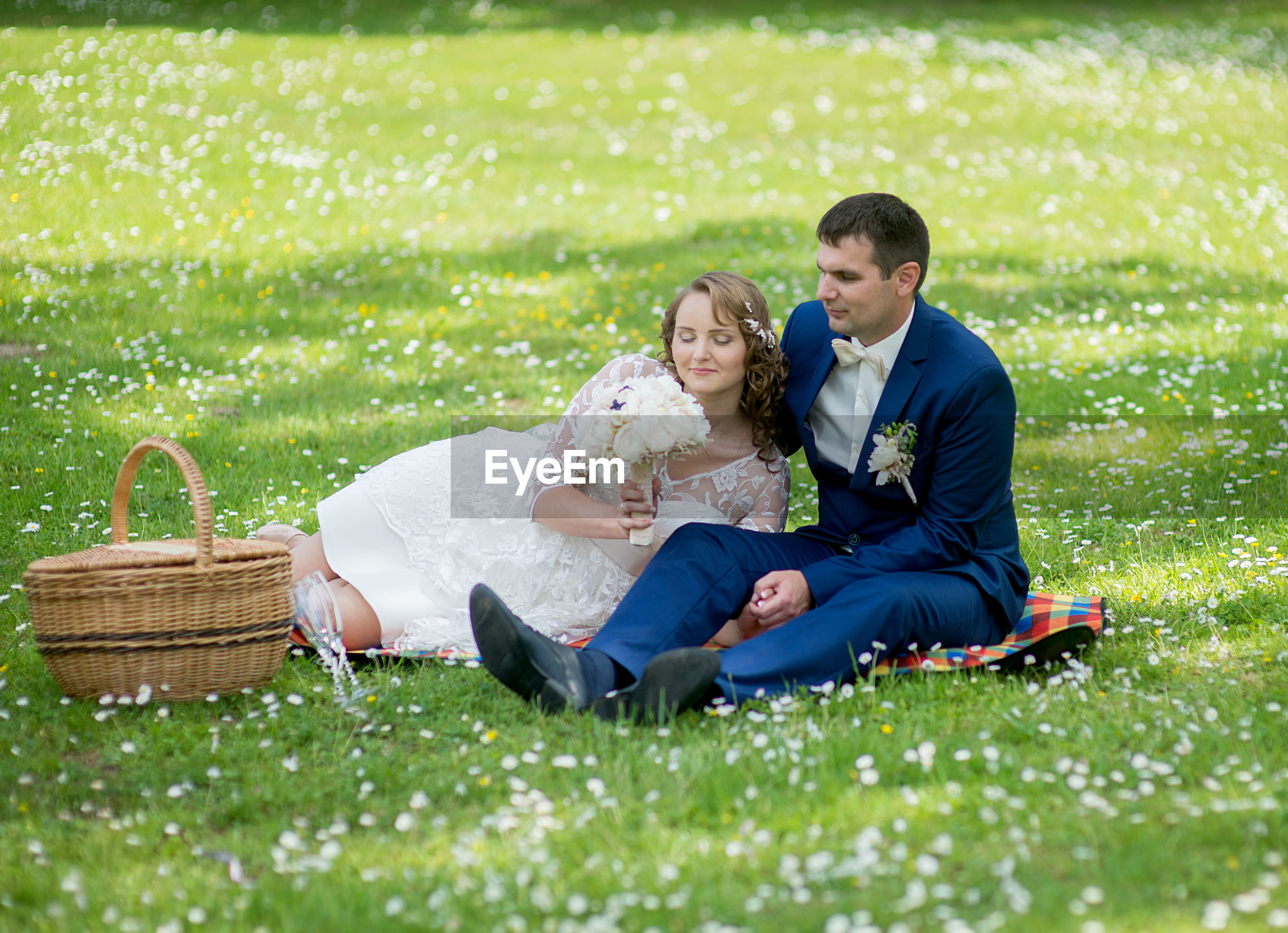 Newlywed couple sitting on picnic blanket at park