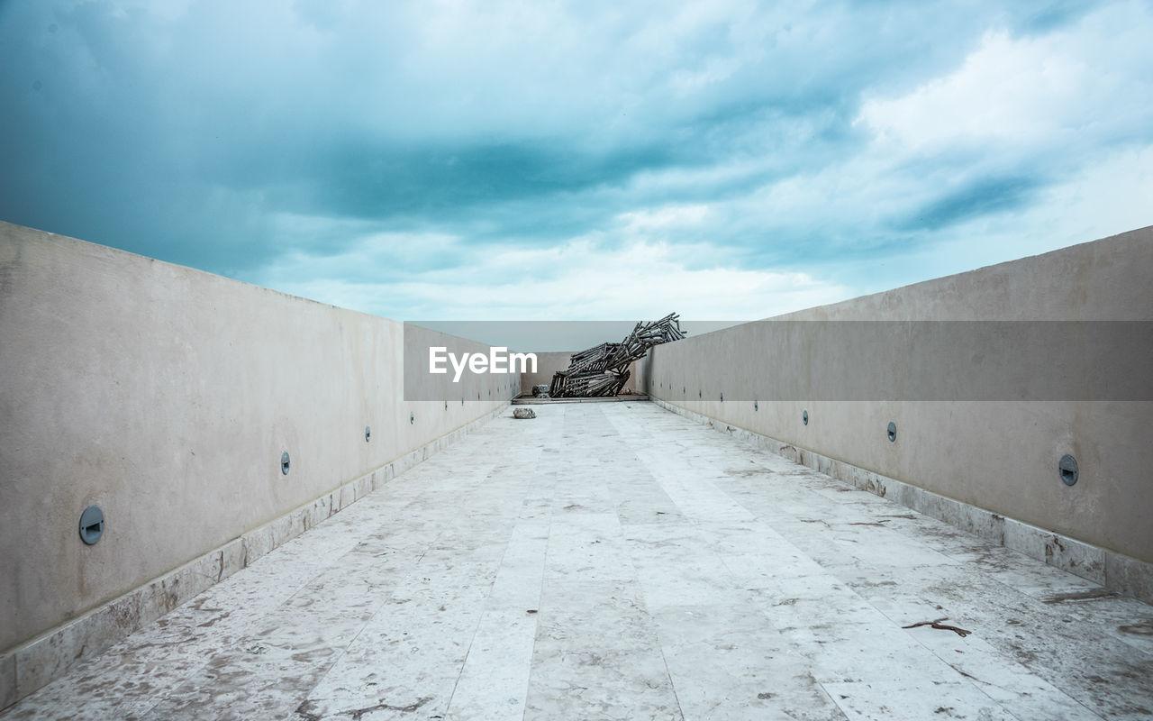 Elevated Walkway Against Cloudy Sky