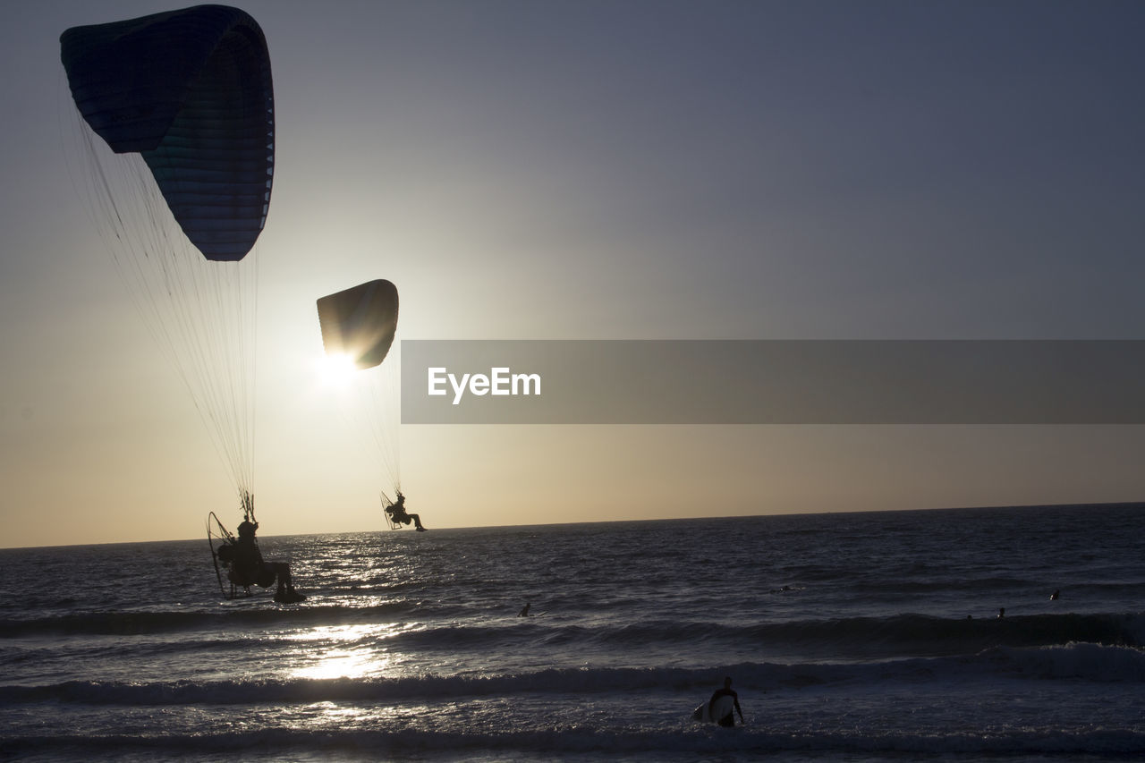 Silhouette People Paragliding Over Sea Against Sky During Sunset
