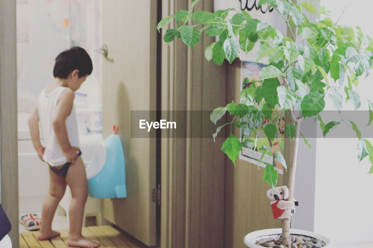 Full Length Of Boy Urinating In Bathroom At Home
